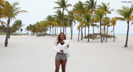 Serena at the beach with cup